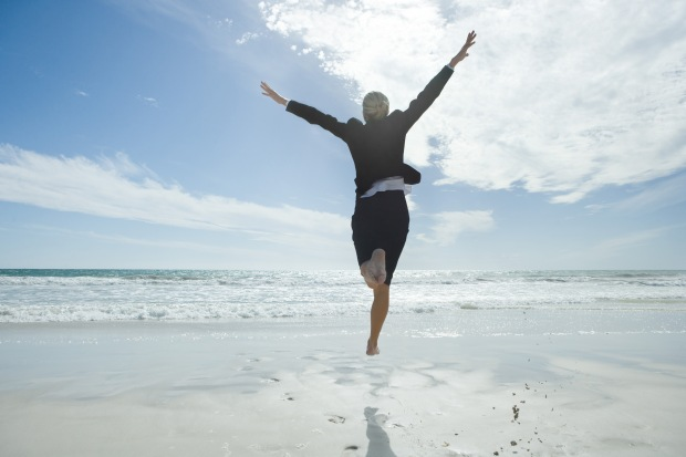 Businesswoman jumping in air on beach, rear view