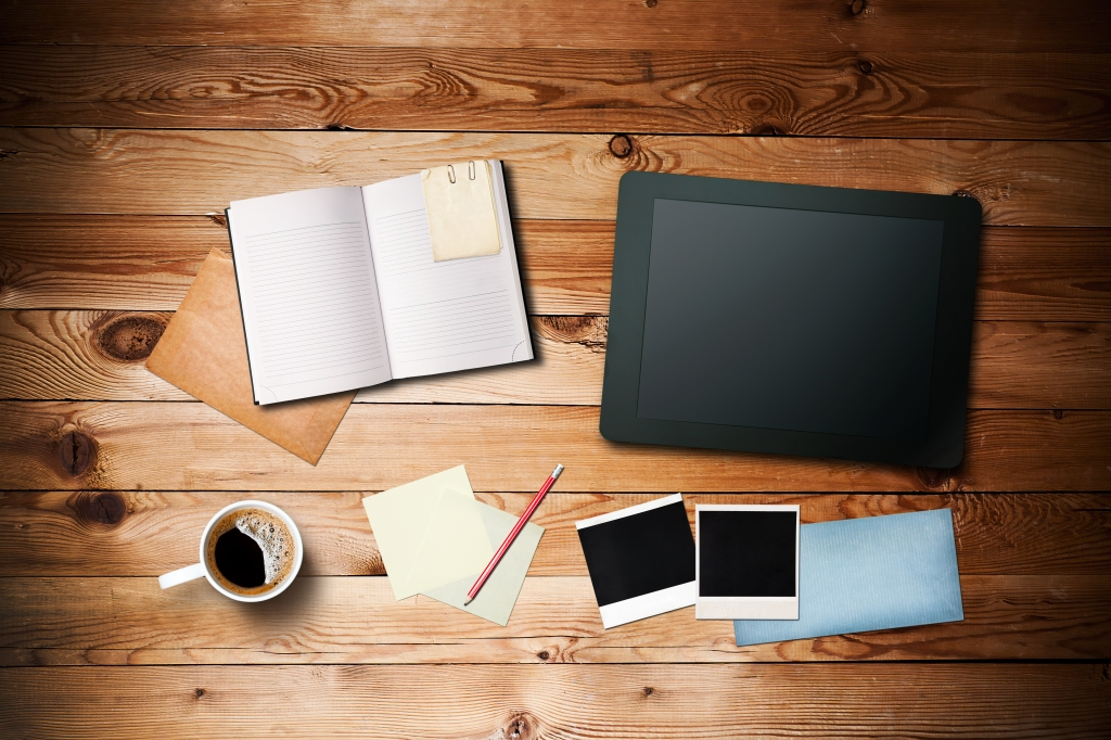 Workspace with coffee cup,  tablet pc, instant photos, note pape